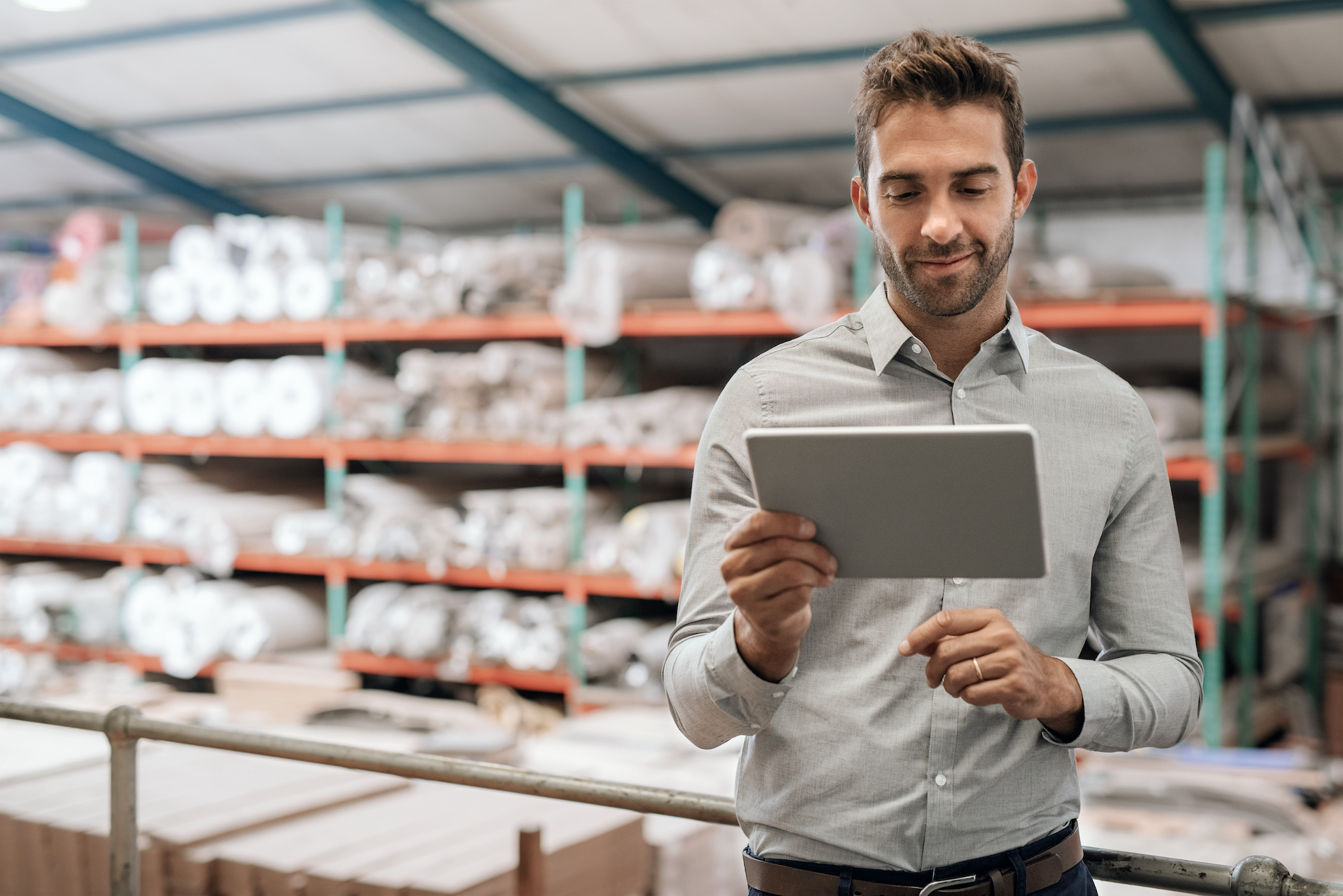 Happy distribution warehouse manager holding a cloud-enabled mobile tablet
