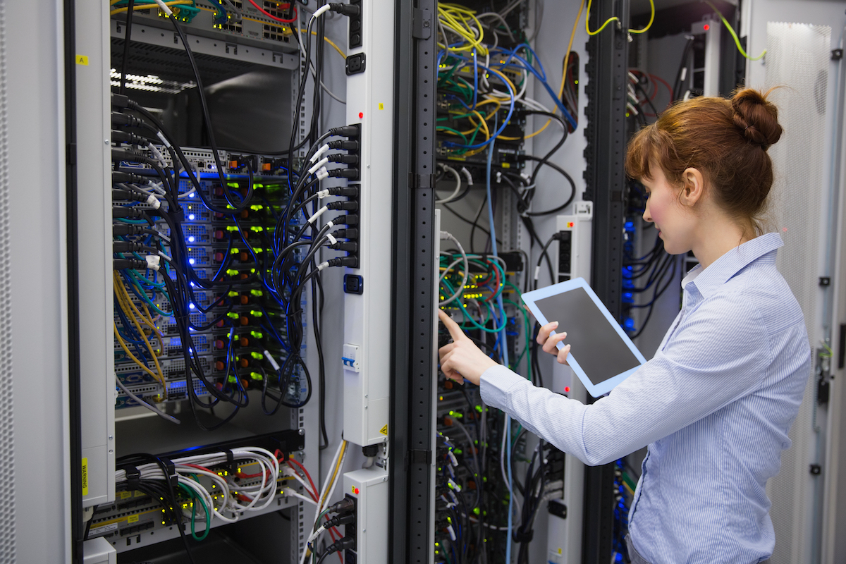 Secure server room with female technology specialist assessing hardware with a mobile device